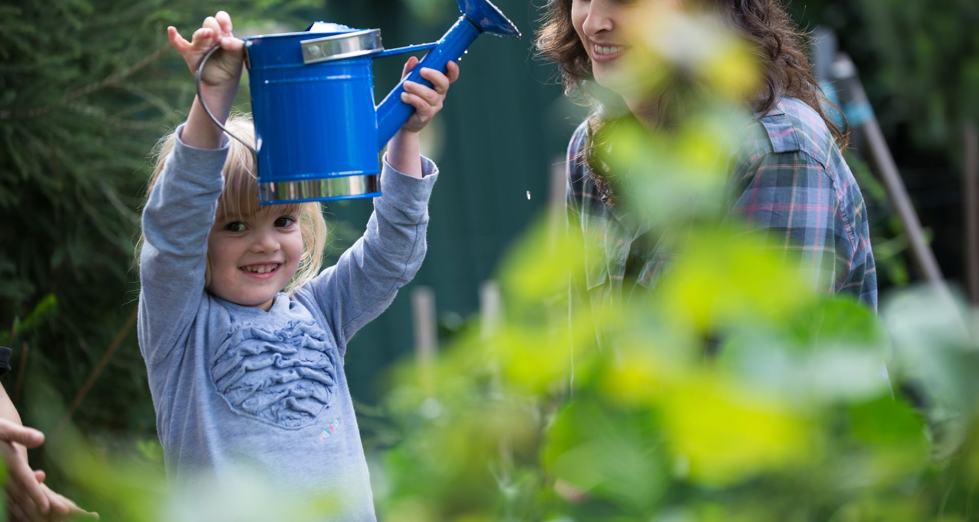 Young Girl Holding A Watering Can In Home Garden